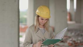 Ο θηλυκός μηχανικός είναι 0 και ανατρεμμένος διαβάζοντας το σχέδιο κατασκευής απόθεμα βίντεο