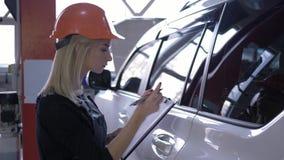 Ο θηλυκός μηχανικός στο κράνος εξετάζει τον όρο του άσπρου αυτοκινήτου και παίρνει τις σημειώσεις στην περιοχή αποκομμάτων στο πρ απόθεμα βίντεο