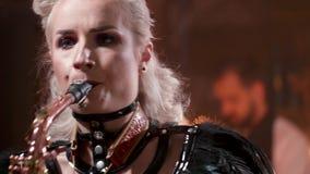 Ο θηλυκός μουσικός παίζει ένα τραγούδι σε ένα saxophone απόθεμα βίντεο