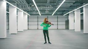 Ο θηλυκός μουσικός παίζει το βιολί στην κενή αίθουσα απόθεμα βίντεο