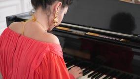 Ο θηλυκός μουσικός στο κομψό φόρεμα και τα κομψά σκουλαρίκια παίζουν το πιάνο σε σε αργή κίνηση φιλμ μικρού μήκους