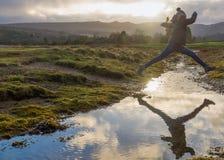 Ο θηλυκός οδοιπόρος πηδά το ρεύμα σε Arran Σκωτία Στοκ φωτογραφία με δικαίωμα ελεύθερης χρήσης