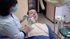 Ο θηλυκός οδοντίατρος κινηματογραφήσεων σε πρώτο πλάνο εξετάζει τα υπομονετικά δόντια με μια ενδοστοματική κάμερα Θεραπεία και πρ φιλμ μικρού μήκους