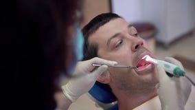 Ο θηλυκός οδοντίατρος κινηματογραφήσεων σε πρώτο πλάνο εξετάζει τα υπομονετικά δόντια με μια ενδοστοματική κάμερα Θεραπεία και πρ απόθεμα βίντεο