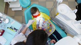 Ο θηλυκός οδοντίατρος μεταχειρίζεται τα δόντια ενός νέου αγοριού Να πυροβολήσει άνωθεν απόθεμα βίντεο