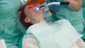 Ο θηλυκός οδοντίατρος με έναν βοηθό πραγματοποιεί τα δόντια που λευκαίνουν τη διαδικασία φιλμ μικρού μήκους