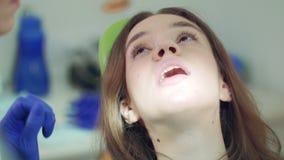 Ο θηλυκός οδοντίατρος παίρνει έξω tampon βαμβακιού από το ανοικτό υπομονετικό στόμα απόθεμα βίντεο