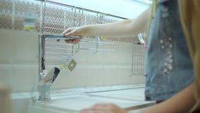 Ο θηλυκός πελάτης αγγίζει τη στρόφιγγα κουζινών μετάλλων σε μια προθήκη στο κατάστημα απόθεμα βίντεο
