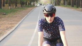 Ο θηλυκός ποδηλάτης οδηγά το ποδήλατο στο πάρκο Το μέτωπο ακολουθεί τον πυροβολισμό Έννοια ανακύκλωσης φιλμ μικρού μήκους