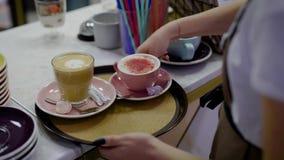 Ο θηλυκός σερβιτόρος βάζει επιδόρπιο και δύο κούπες με το γλυκό καφέ σε έναν στρογγυλό δίσκο και το μεταφέρει στην αίθουσα καφέδω απόθεμα βίντεο