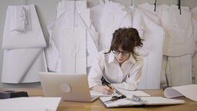 Ο θηλυκός σχεδιαστής εξετάζει το lap-top στο υπόβαθρο των σχεδίων απόθεμα βίντεο