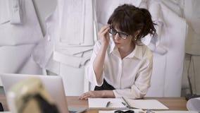Ο θηλυκός σχεδιαστής εργάζεται με το lap-top στον πίνακα στο ράψιμο του στούντιο απόθεμα βίντεο