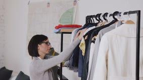 Ο θηλυκός σχεδιαστής μόδας εργάζεται στη νέα συλλογή για τους πελάτες στο άνετο στούντιο εργαστηρίων, μοδίστρα, ράφτης ή needlewo φιλμ μικρού μήκους