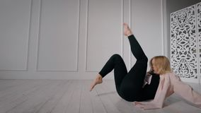 Ο θηλυκός σύγχρονος χορευτής εκπαιδεύει στην αίθουσα χορού μόνο, καθμένος στο πάτωμα, που κινεί τα πόδια επάνω απόθεμα βίντεο