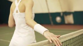 Ο θηλυκός τενίστας τρέχει το χέρι της κατά μήκος του διχτυού Στο εσωτερικό μήκος σε πόδηα, καλυμμένη περιοχή δικαστηρίων απόθεμα βίντεο
