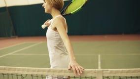 Ο θηλυκός τενίστας τρέχει το χέρι της κατά μήκος του διχτυού Στο εσωτερικό μήκος σε πόδηα, καλυμμένη περιοχή δικαστηρίων φιλμ μικρού μήκους