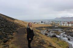 Ο θηλυκός τουρίστας θέτει δίπλα στο χαρακτηριστικό ισλανδικό τοπίο στοκ εικόνα