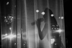 Ο θηλυκός τραγουδιστής πίσω από το μικρόφωνο κουρτινών τραγουδά στοκ φωτογραφία