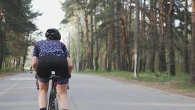 Ο θηλυκός χαριτωμένος ποδηλάτης οδηγά ένα ποδήλατο στο πάρκο ως μέρος της ρουτίνας κατάρτισής της Έννοια ανακύκλωσης o απόθεμα βίντεο