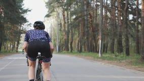 Ο θηλυκός χαριτωμένος ποδηλάτης οδηγά ένα ποδήλατο στο πάρκο ως μέρος της ρουτίνας κατάρτισής της Έννοια ανακύκλωσης απόθεμα βίντεο