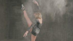 Ο θηλυκός χορευτής μπαλέτου στο μαύρο κοστούμι σωμάτων αποδίδει στη σκηνή στο θέατρο και χρησιμοποίηση της λευκιάς σκόνης ή του λ
