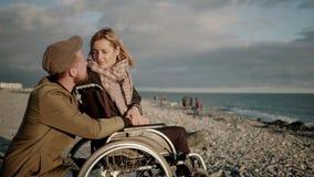Ο θηλυκός χρήστης αναπηρικών καρεκλών και ο φίλος της κουβεντιάζουν και βλέπουν seascape απόθεμα βίντεο