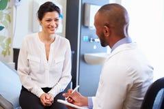 Ο θηλυκοί ασθενής και ο γιατρός διοργανώνουν τις διαβουλεύσεις στο δωμάτιο νοσοκομείων Στοκ Φωτογραφία