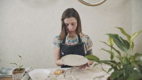 Ο θηλυκός αγγειοπλάστης παρουσιάζει το ολοκληρωμένο προϊόν - ένα κεραμικό πιάτο φιλμ μικρού μήκους
