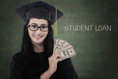 Ο θηλυκός απόφοιτος φοιτητής παίρνει τα χρήματα για το δάνειο Στοκ φωτογραφία με δικαίωμα ελεύθερης χρήσης