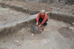 Ο θηλυκός αρχαιολόγος εργάζεται στην ανασκαφή με το αρχαίο κέντρο στοκ φωτογραφίες