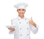 Ο θηλυκός αρχιμάγειρας με την κενή παρουσίαση πιάτων φυλλομετρεί επάνω Στοκ εικόνα με δικαίωμα ελεύθερης χρήσης