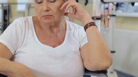 Ο θηλυκός ασθενής κάθεται στην αναπηρική καρέκλα στο νοσοκομείο απόθεμα βίντεο