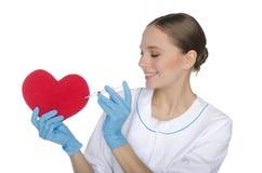 Ο θηλυκός γιατρός με μια σύριγγα τσιμπεί το σύμβολο καρδιών Στοκ εικόνα με δικαίωμα ελεύθερης χρήσης