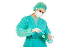 Ο θηλυκός γιατρός χειρούργων με ένα χειρουργικό νυστέρι εκτελεί τη χειρουργική επέμβαση Στοκ εικόνα με δικαίωμα ελεύθερης χρήσης
