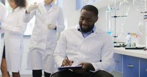 Ο θηλυκός επιστήμονας συζητά το σωλήνα δοκιμής με το συνάδελφο αφροαμερικάνων ενώ ομάδα ερευνητών που κάνει το πείραμα στο εργαστ απόθεμα βίντεο
