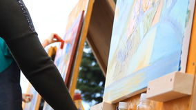 Ο θηλυκός καλλιτέχνης χρωματίζει μια ζωηρόχρωμη εικόνα στο θερινό φεστιβάλ Ένας άλλος βιοτέχνης με τον κύλινδρο χρωμάτων στο υπόβ φιλμ μικρού μήκους