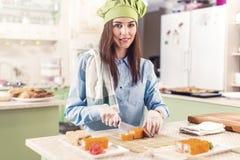 Ο θηλυκός μάγειρας που φορά το καπέλο και τα γάντια αρχιμαγείρων s που κατασκευάζουν τα ιαπωνικά σούσια κυλά, χαμόγελο, εξετάζοντ Στοκ Φωτογραφίες