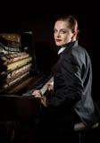 Ο θηλυκός μουσικός έντυσε σε μια συνεδρίαση κοστουμιών ατόμων ` s δίπλα στο πιάνο Στοκ εικόνες με δικαίωμα ελεύθερης χρήσης