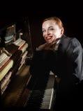 Ο θηλυκός μουσικός έντυσε σε μια συνεδρίαση κοστουμιών ατόμων ` s δίπλα στο πιάνο Στοκ Εικόνες