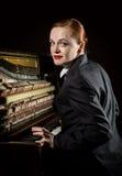 Ο θηλυκός μουσικός έντυσε σε μια συνεδρίαση κοστουμιών ατόμων ` s δίπλα στο πιάνο Στοκ φωτογραφία με δικαίωμα ελεύθερης χρήσης
