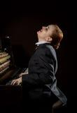 Ο θηλυκός μουσικός έντυσε σε μια συνεδρίαση κοστουμιών ατόμων ` s δίπλα στο πιάνο Στοκ Εικόνα