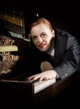 Ο θηλυκός μουσικός που ντύνεται σε ένα κοστούμι ατόμων ` s βρίσκεται σε ένα πληκτρολόγιο πιάνων Στοκ Εικόνες