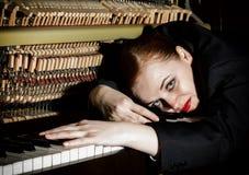 Ο θηλυκός μουσικός που ντύνεται σε ένα κοστούμι ατόμων ` s βρίσκεται σε ένα πληκτρολόγιο πιάνων Στοκ Εικόνα