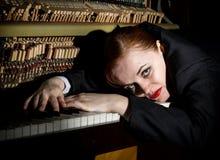 Ο θηλυκός μουσικός που ντύνεται σε ένα κοστούμι ατόμων ` s βρίσκεται σε ένα πληκτρολόγιο πιάνων Στοκ φωτογραφίες με δικαίωμα ελεύθερης χρήσης