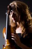 Ο θηλυκός μουσικός φορέας ενάντια στο σκοτάδι Στοκ φωτογραφία με δικαίωμα ελεύθερης χρήσης