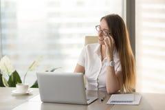 Ο θηλυκός οικονομικός σύμβουλος συμβουλεύεται τους πελάτες τηλεφωνικώς Στοκ Φωτογραφίες