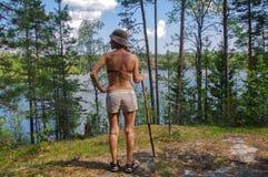 Ο θηλυκός οδοιπόρος που στέκεται στο δύσκολο ίχνος και τη waching κυανή κατάπληξη χρωματίζει το δασικό υπόβαθρο λιμνών βουνών Στοκ Φωτογραφία