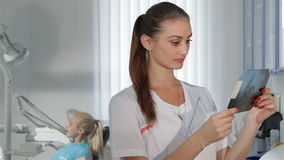 Ο θηλυκός οδοντίατρος εξετάζει την των ακτίνων X εικόνα στην οδοντική κλινική φιλμ μικρού μήκους