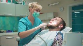 Ο θηλυκός οδοντίατρος που εξετάζει τα δόντια του αρσενικού ασθενή, κοιτάζει στη κάμερα πυροβολισμός ολισθαινόντων ρυθμιστών φιλμ μικρού μήκους