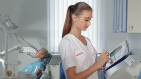 Ο θηλυκός οδοντίατρος χαρακτηρίζει κάτι στο περιοδικό της στο γραφείο οδοντιάτρων φιλμ μικρού μήκους
